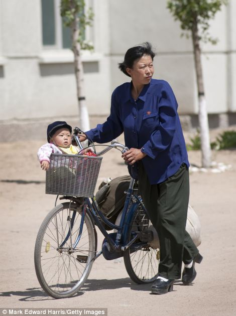 Mother and child in front of the  Tumangang train station, taken in July 2011