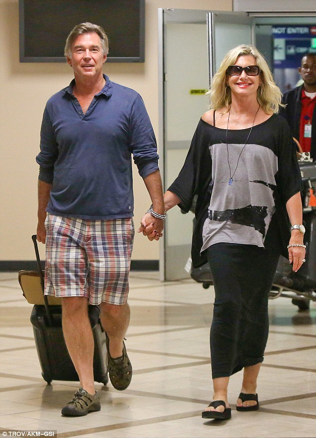 Airport chic: Olivia wore a black maxi-skirt, oversized black and grey top and sandals as she emerged from the flight, while hubby John teamed colourful plaid shorts with a navy blue jersey and sneakers