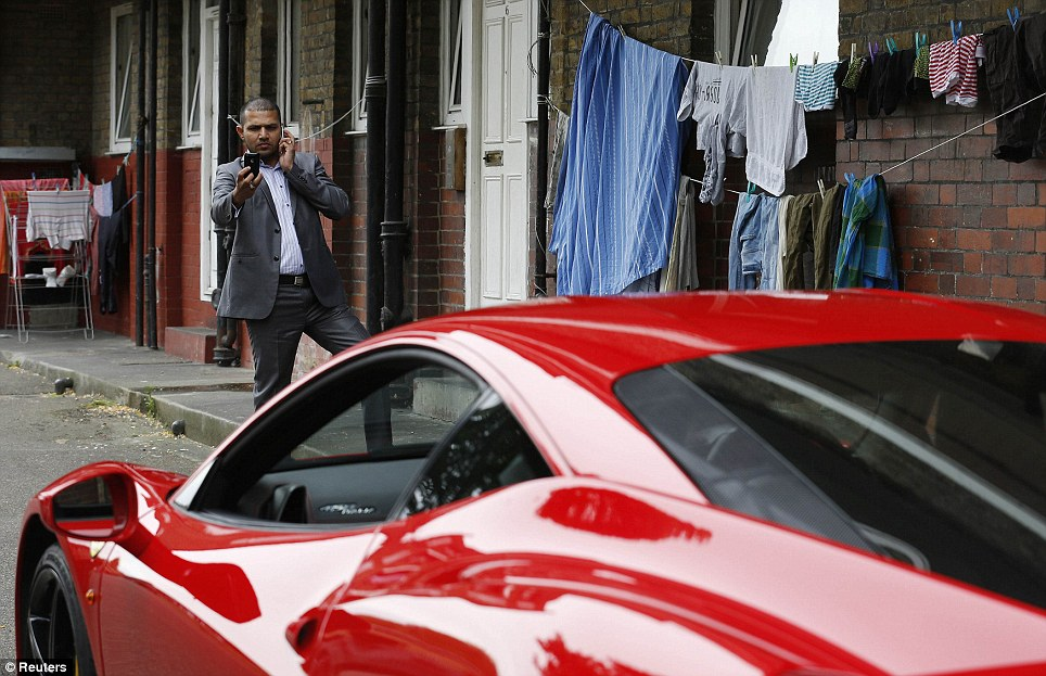 Admiring: A man photographs this parked supercar while chatting on another mobile phone, with a makeshift washing line to his left