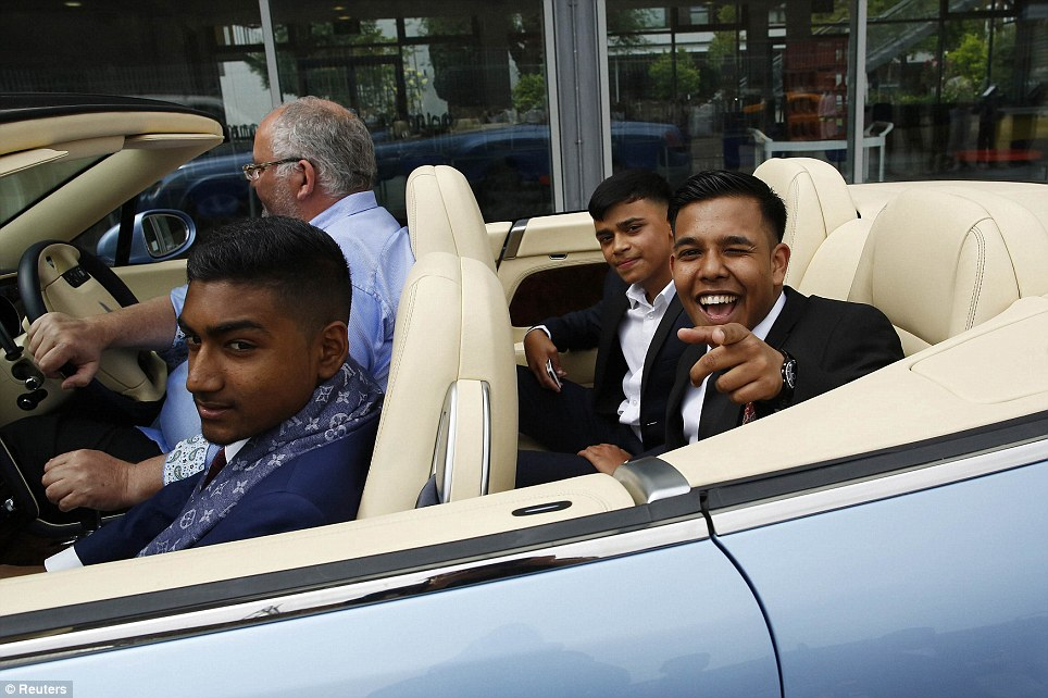Having fun: Rezaul Alom, 16, points at the camera as he drives past with Mahir Magnet Choudhury (L), and Nazmul Islam (2nd R) in the Bentley they hired