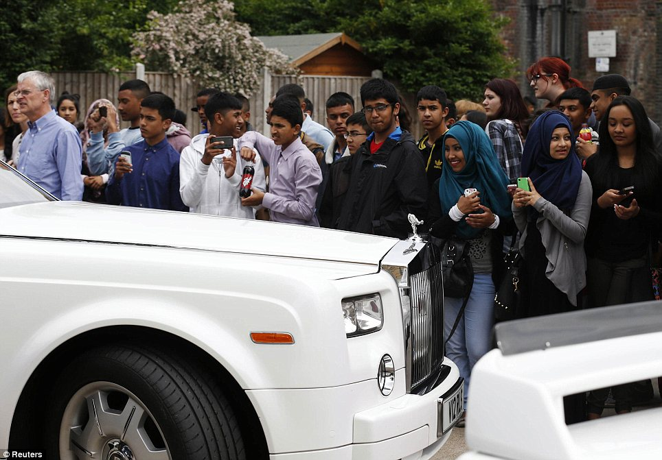 High-rollers: Students and onlookers watch as a Rolls Royce sweeps into school, with many taking photos om their phones