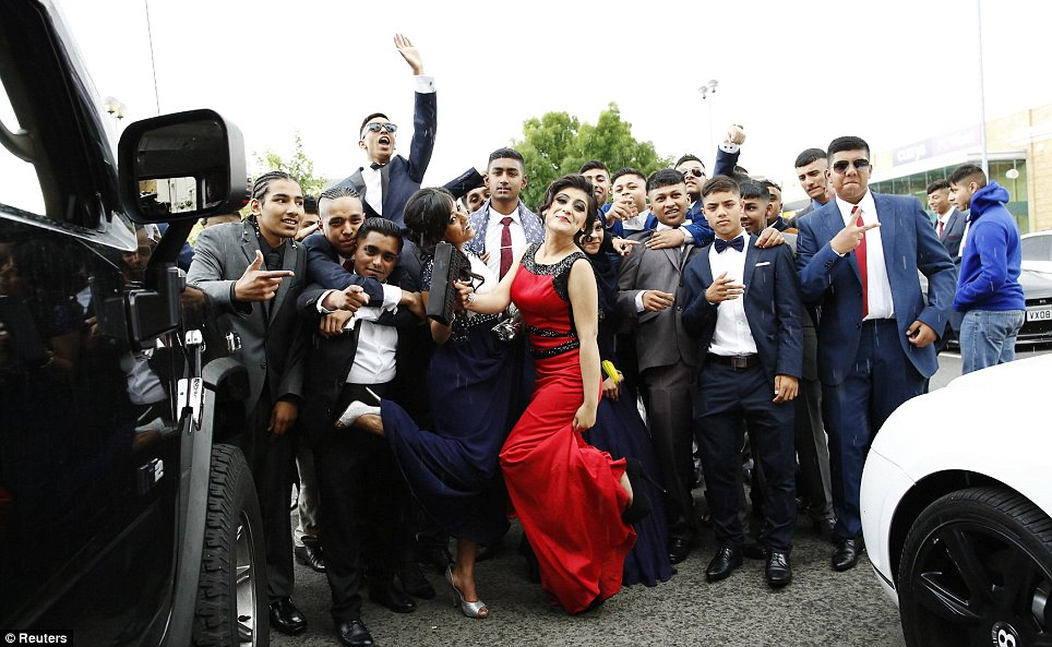 Good crowd: Morpeth School students pose for a group photograph between two super expensive cars on a say they'll remember forever
