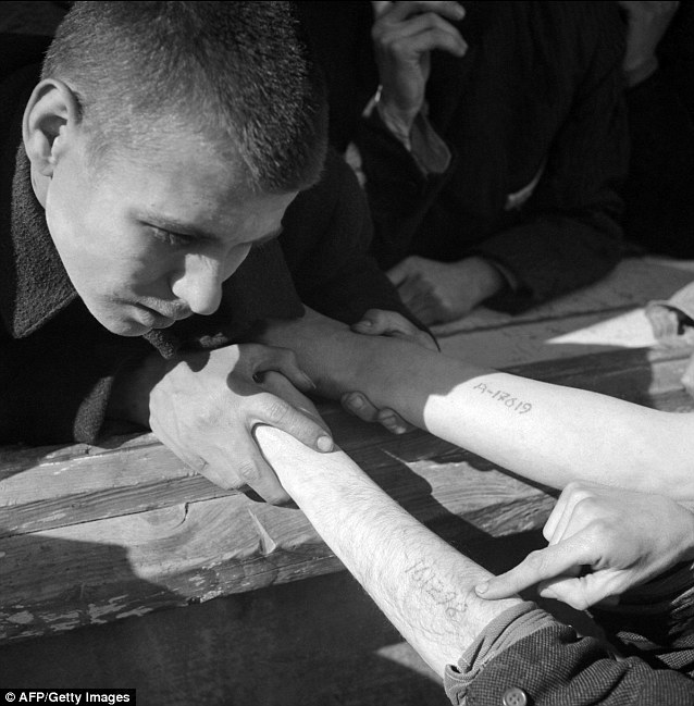 Nightmarish: A young man checks numbers tattooed on the arms of Jewish Polish prisoners coming from the infamous Auschwitz concentration camp