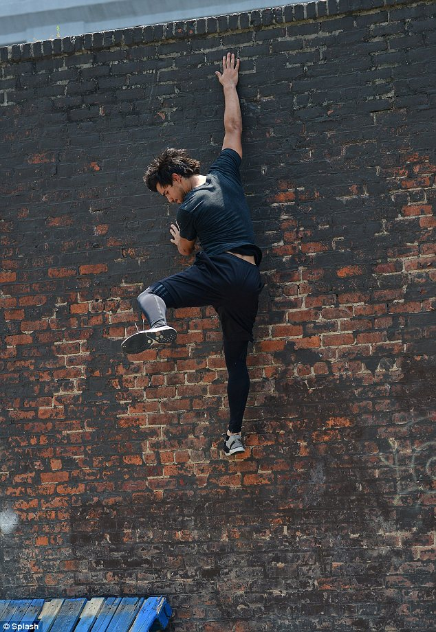 Action hero: The Twilight star, who was dressed in workout wear, was seen scaling a wall for one of his stunts