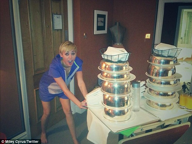 'Yummmm': Miley tweeted a snap of herself appearing to drag a room service tray into her hotel suite