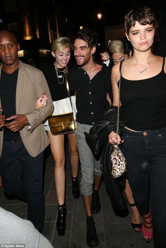 High spirits: Miley looked to be having fun on the night out as she put her arm around a male companion