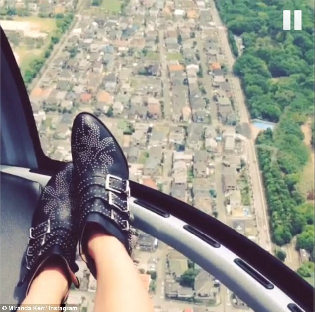 Enjoying the view: Miranda shared a picture of what she was seeing from the air, as well as her cute boots, tweeting: 'Flying high'