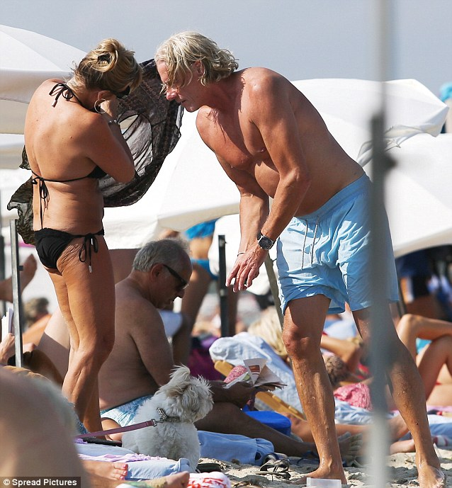 Helping hand: Björn lends wife Patricia a hand with her sarong on the beach