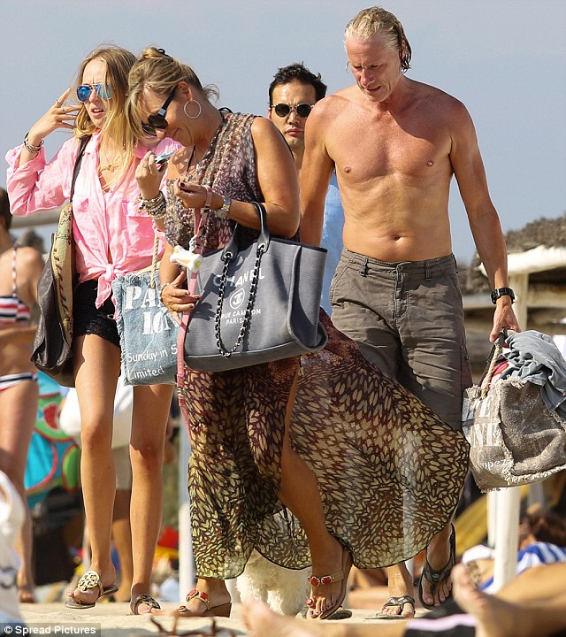 That's enough fun for today: Björn puts on a pair of brown shorts and Patricia a printed dress holding a Chanel handbag as the family leave Club 55 for the day