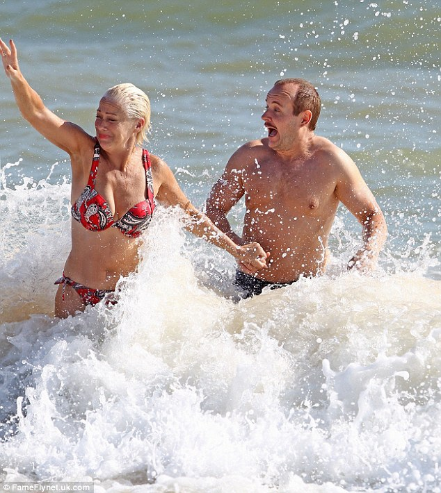 Surf's up: The pair hold hands as they splash in the sea