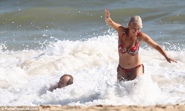 Splash: Lincoln is knocked over by a wave as Denise manages to stay on her feet