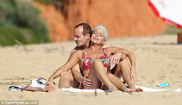 Bliss: The couple looked relaxed and happy as they cuddled on the beach