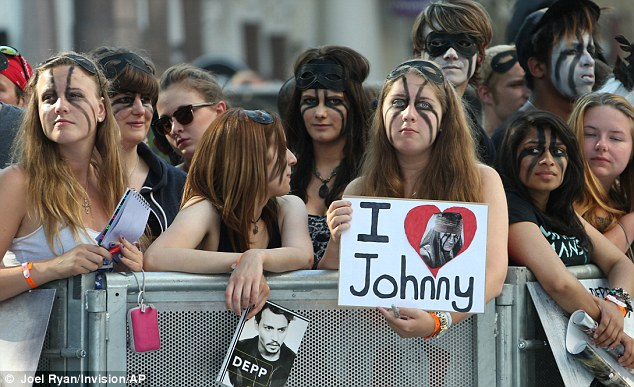 Devotees: Scores of fans came dressed for the movie and held up signs showing their love for Depp