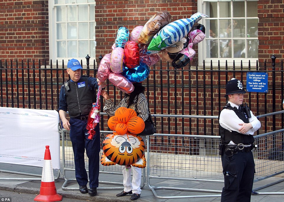 Gifts: Police take a set of balloons from a woman standing at a barrier outside the hospital as monarchists arrive for the birth