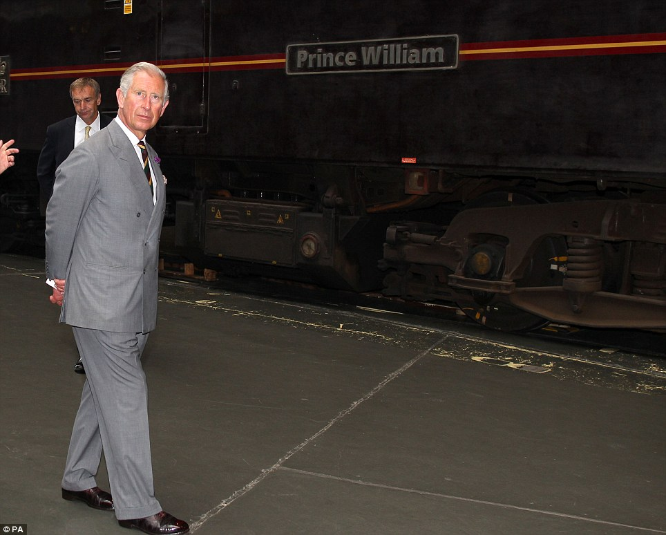 Calm: Prince Charles strolls with his hands behind his back as he passes a train named after his son, who later became a father himself