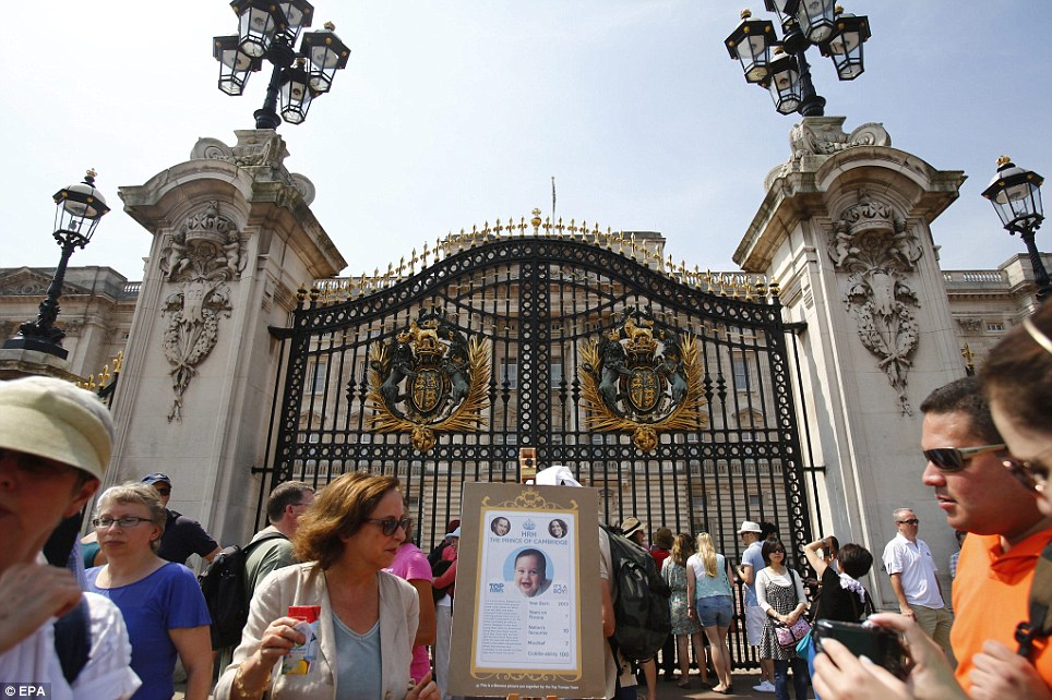 Flashback: A bogus easel similar to the one that will be used to announce the royal baby's birth is placed outside the Palace as tourists mill around