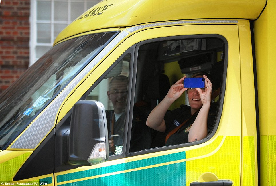 Laughter: An excited member of the ambulance crew takes a photo of the media outside the Lindo Wing