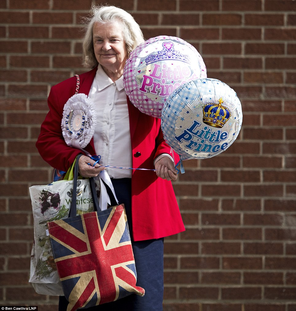 Big fan: Margaret Tyler clutches her royal baby balloons outside the hospital as the world waits for the royal baby
