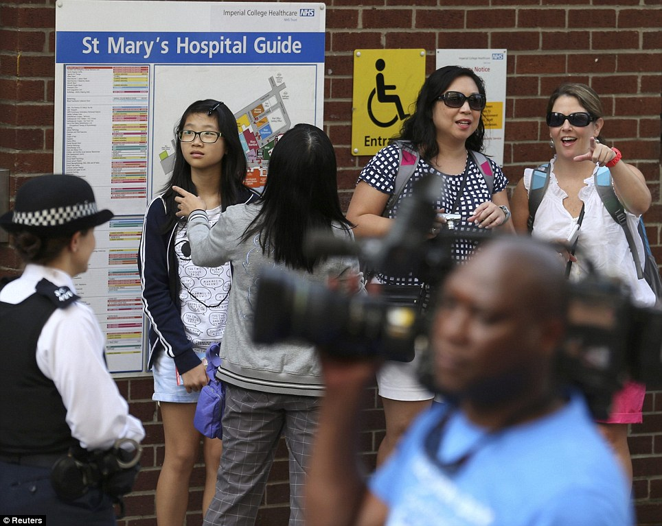 Royal fans: Tourists look at the gathering media scrum outside the hospital this morning