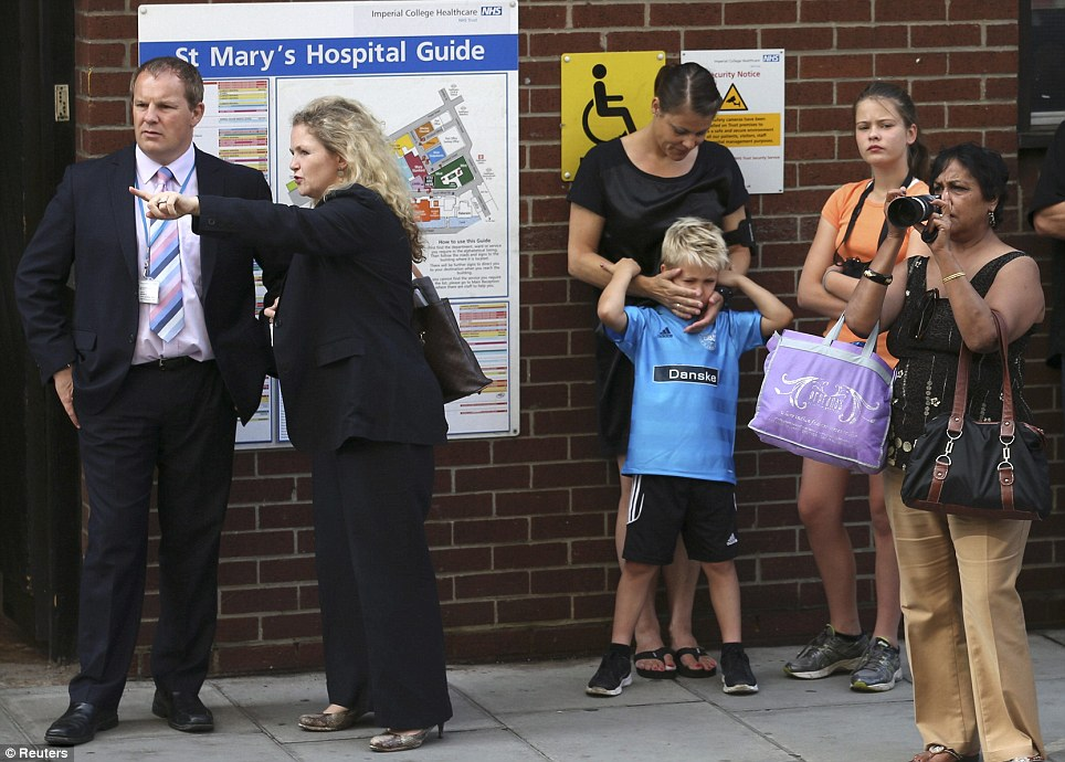 Crowd gathers: Onlookers come and stand outside the hospital - and look at the media scrum - after it emerged that the Duchess had gone into labour