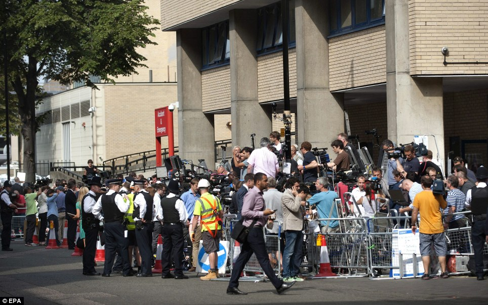 Pack: Police and the international media seen outside the Lindo Wing waiting for news about Kate, 31, who had gone into labour