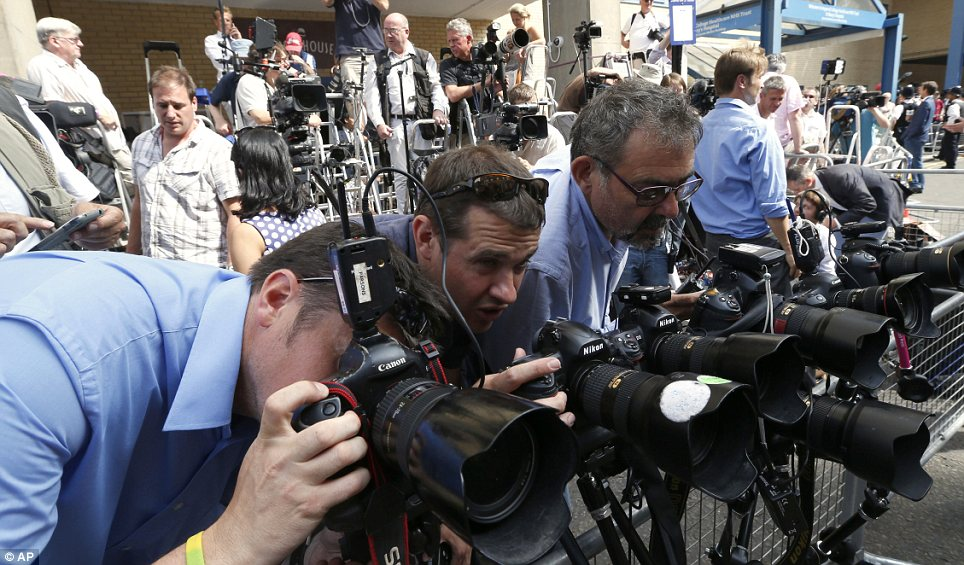 Capturing the moment: Photographers adjust their cameras outside the hospital