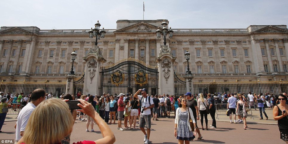 Souvenir: A tourist takes a photo of the scene at the Palace today, waiting for the announcement of the birth