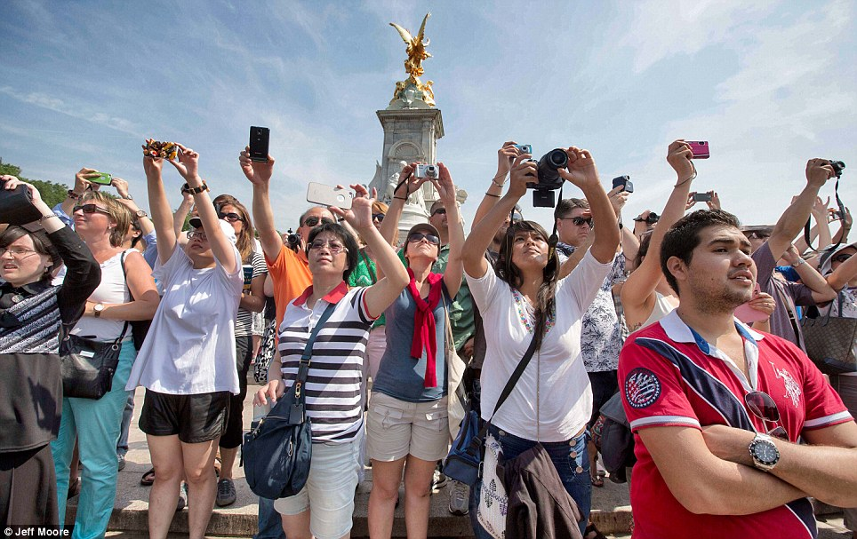 Royal fans: Camera phones and cameras are held aloft outside Buckingham Palace this afternoon