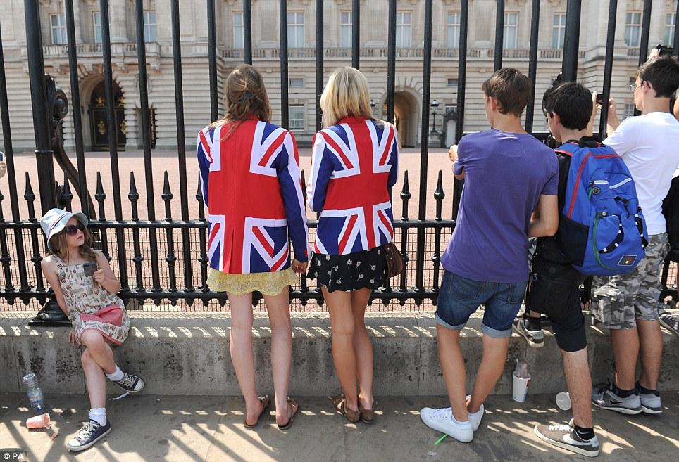 Royal fans: A young girl looks-on as Royal well wishers Sarah Haggie, left, and Fi Thompson, right, pose in Union flag themed jackets outside Buckingham Palace in central London