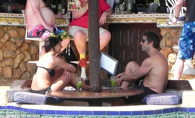 Relaxed: Onlookers told the paper he bought mojitos and tequila shots for the bikini-clad brunette all day last Thursday as they relaxed by the pool