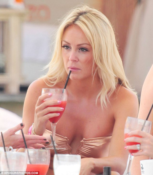 Bottoms up: Gill was seen sipping on her drink and chatting to friends