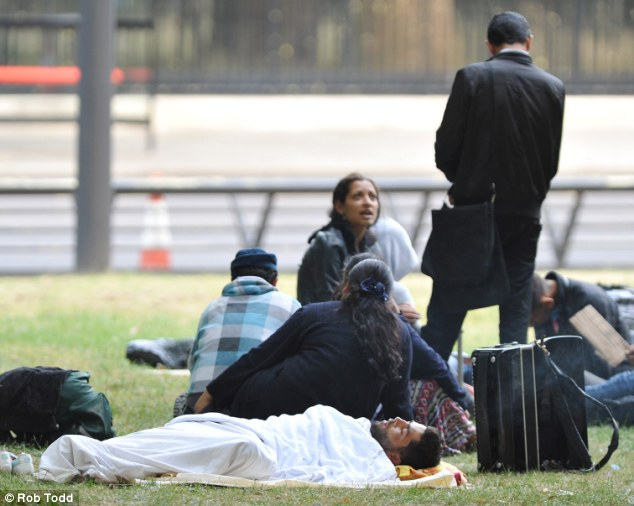 Return of the Roma: A group discussion goes on in the background as one man is still asleep on the grass in the early hours of the morning
