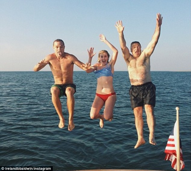 Summer fun: Ireland Baldwin tweeted this photo last week of her flanked by boyfriend Slater Trout and her father