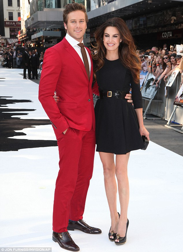 Smart: Armie looked dapper at the UK premiere on Sunday night in a red suit, while his wife wore a LBD