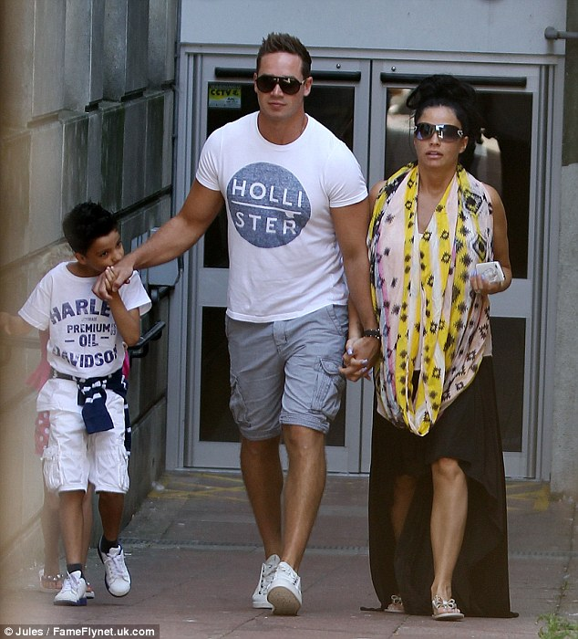 Kisses: Kieran seems to be close to his wife Katie's two young children Junior and Princess