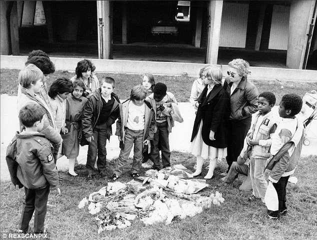 Scene of the killing: Residents and children lay flowers in memory of Pc Blakelock after he was stabbed to death in Tottenham, north London, in 1985