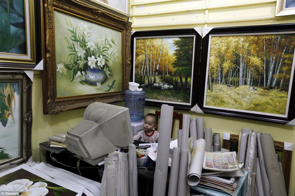 Start them young: A two-year-old boy, the son of a vendor, sits watching cartoons on an old computer surrounded by dozens of rolled up and hanging canvases at a gallery at Dafen