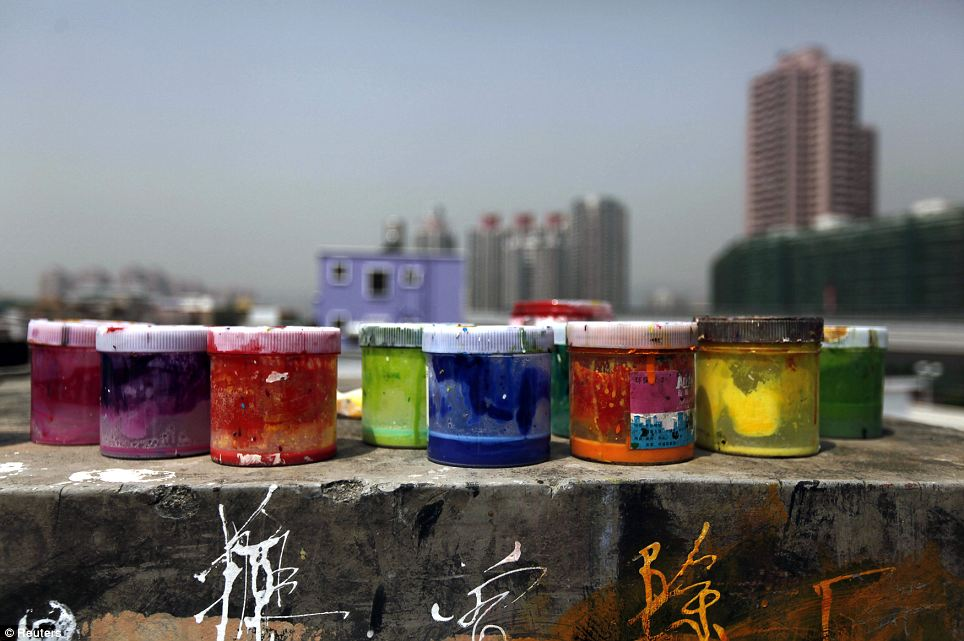 Living life in colour: Pigment tins are placed on the roof of a studio, on a wall where Chinese symbols have been elegantly scrawled by artists
