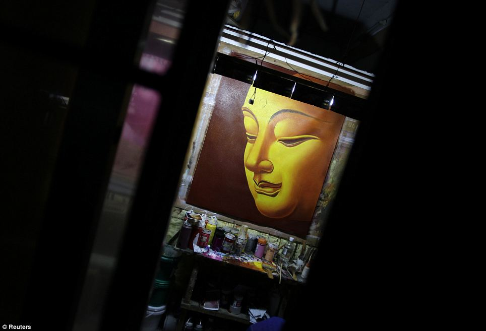 An oil painting of Buddha is seen through window grills: According to one local paper report, exports from Dafen fell more than half in the first six months of last year