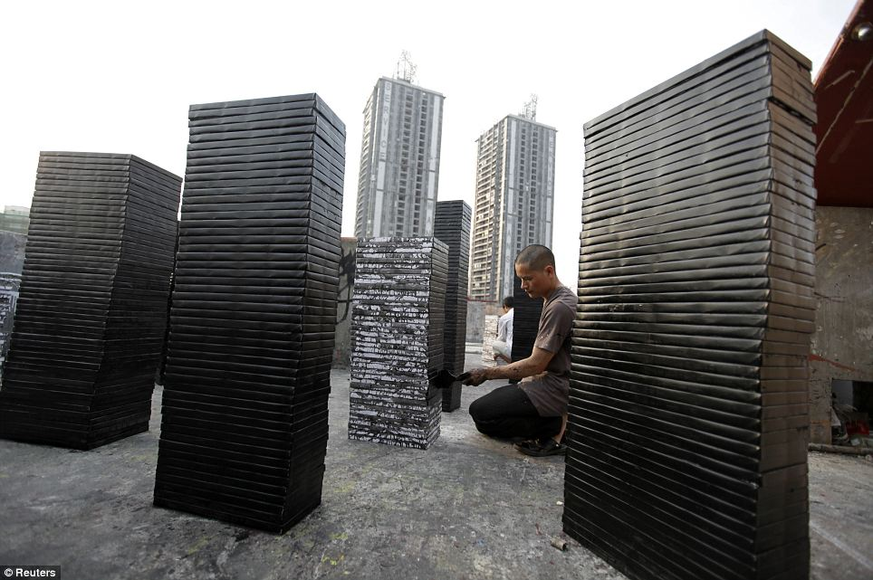 Painters paint picture frames black on the roof of a studio: The simple black frames pictured here are the kinds which are preferred by art buyers in the East