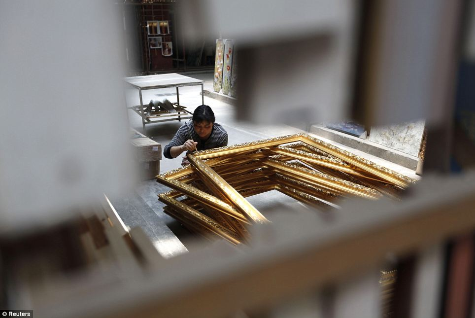 A woman decorates heavy, gilded frames outside a gallery: Thousands of artists work in Dafen, producing paintings which sell online for an average of £40 each