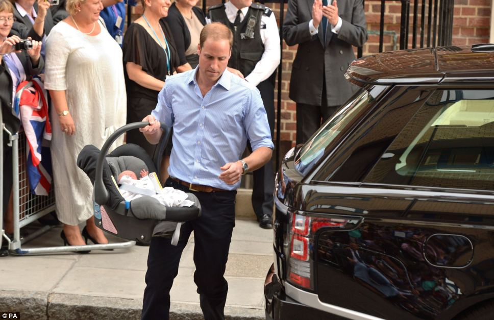 Safe and snug: Prince William carries his day old son to the car in his car seat