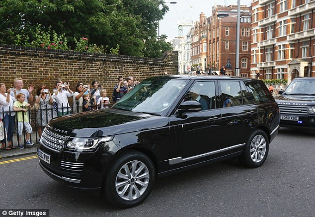 Celebration: Crowds of people waved and cheered as the young family headed into their home