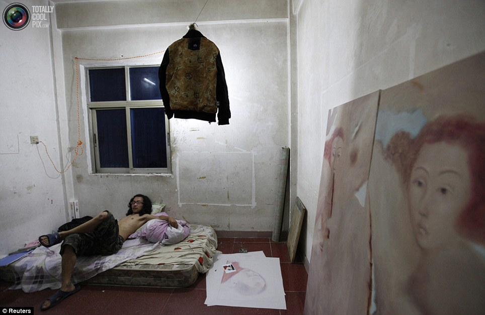 Bare: An artist relaxes in his austere accommodation, overlooked by a portrait of a beautiful woman