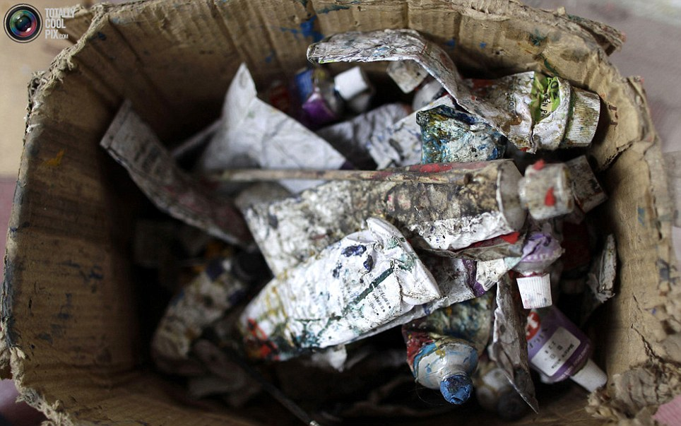 Discarded paint tubes fill a cardboard box