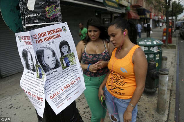 Hopeful: Locals examine a poster put up by police in July 2013 in the area where Baby Hope was found in New York City