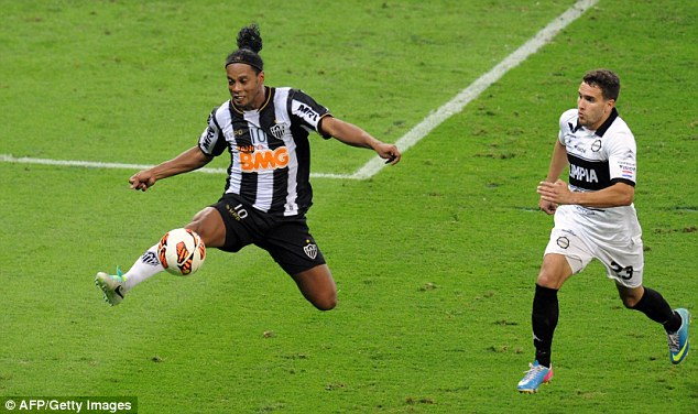 Spring in his step: Ronaldinho jumps to take control of the ball