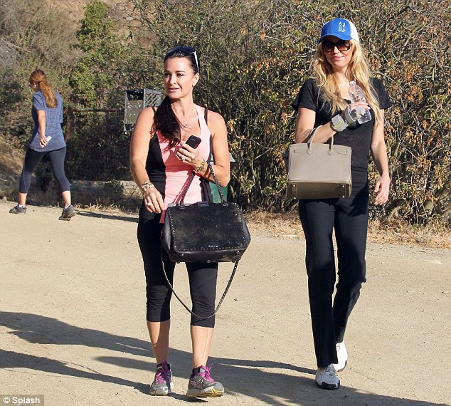 Stylish sweat session: Kyle and Brandi wore tight-fitting workout clothes that complimented their giant purses
