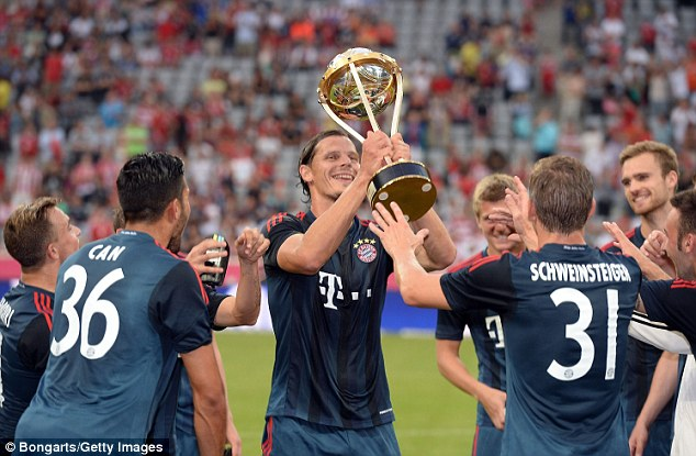 Get used to this: Bayern Munich players, including Daniel van Buyten (centre) celebrate after their win