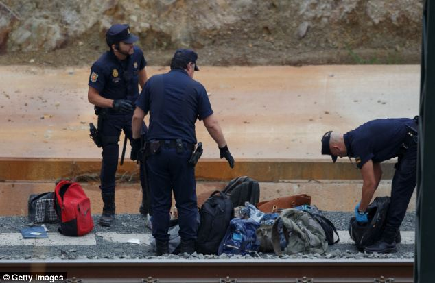 Belongings: Police officers collect baggage at the scene of a train crash